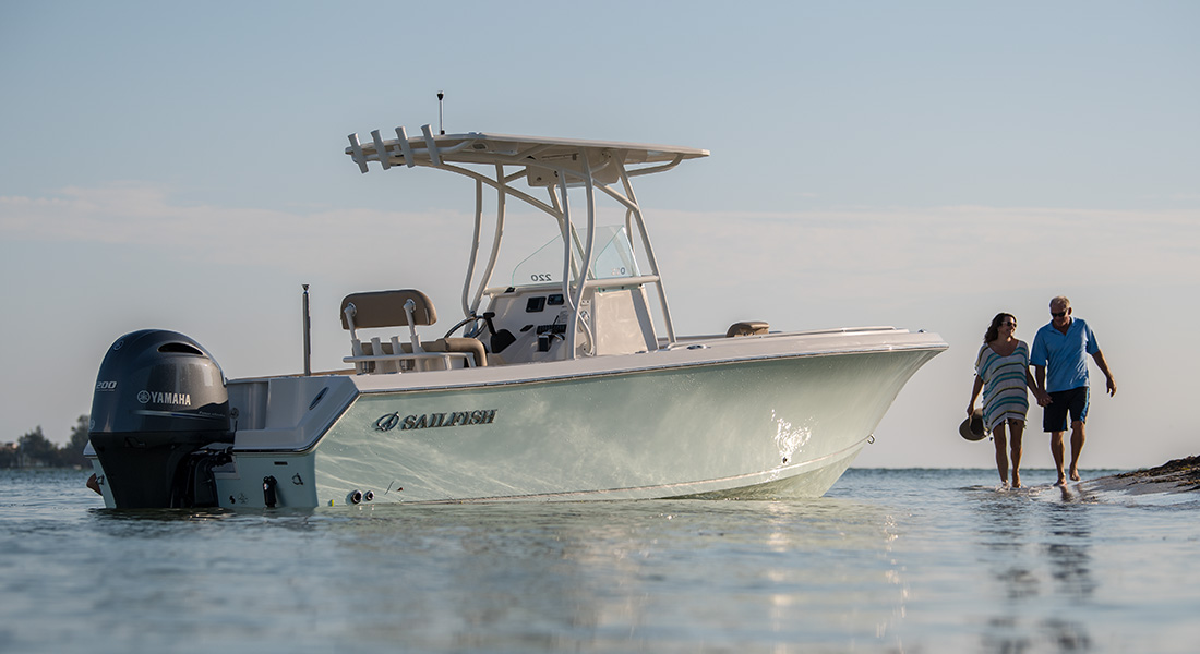 220 Center Console - Couple strolling along beach near beached boat